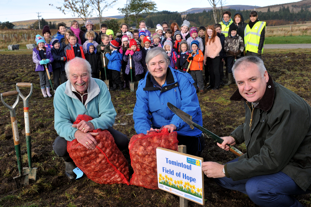 Planting daffodils in the new Tomintoul Field of Hope. Mike and Des Budd  with Richard Lochhead, MSP, front, and pupils of Tomintoul Primary School, who are helping to plant the bulbs, back. Picture by Gordon Lennox.