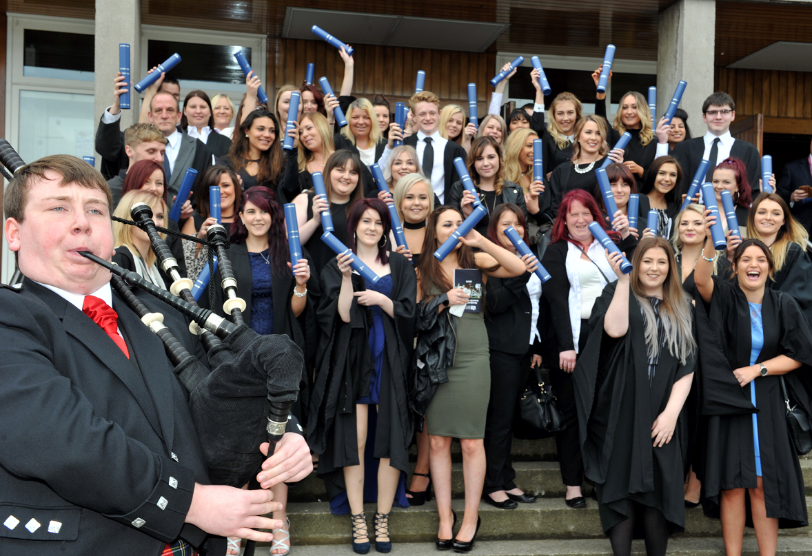 Graduates celebrate their new qualifications on the steps of Elgin Town Hall.