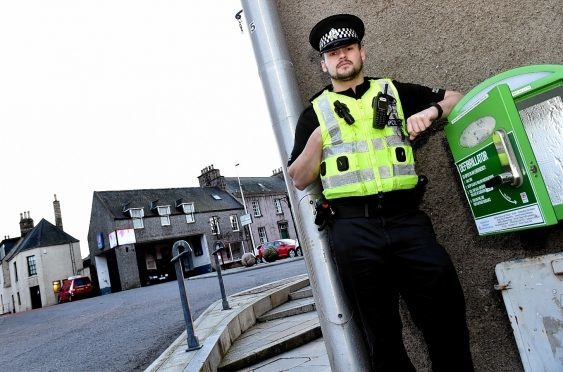 PC Scott Dowie pictured last year in Oldmeldrum, where the defibrillator is kept. Picture by COLIN RENNIE