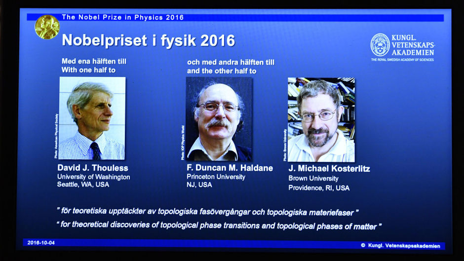 An overhead projector displays the photos of the winners of the Nobel Prize in physics, at the Royal Swedish Academy of Sciences, in Stockholm, Sweden (Anders Wiklund/TT via AP)