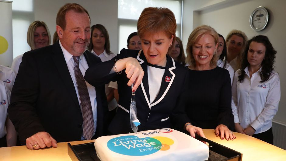 First Minister Nicola Sturgeon cuts a cake to mark an increase in the living wage