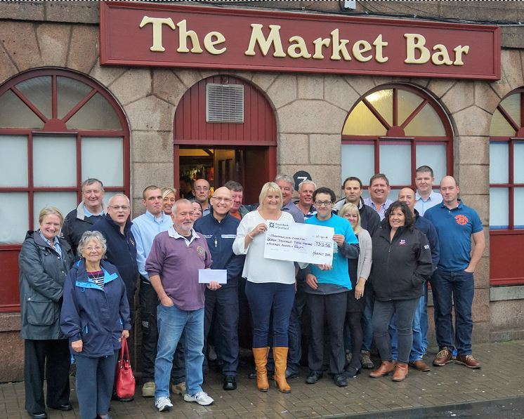 Lorna Anderson handing the cheque over outside her Market Bar