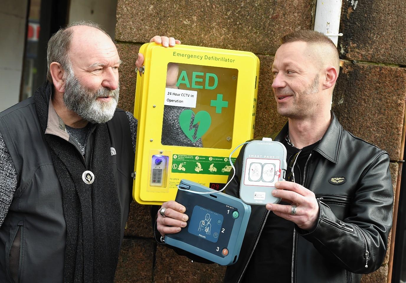 (from left) Stonehaven and District Community Council's Phil Mills-Bishop with John Trudgill from Baker Hughes who have donated four defibrillators to Stonehaven, one of which is now operational in the Market Square.