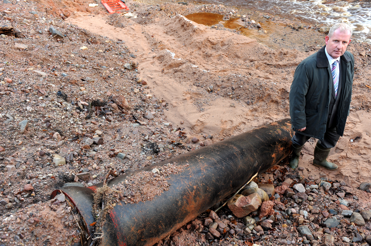Burnside Caravan Park owner Gordon Christie in 2009 next to the pipe responsible for the damage.