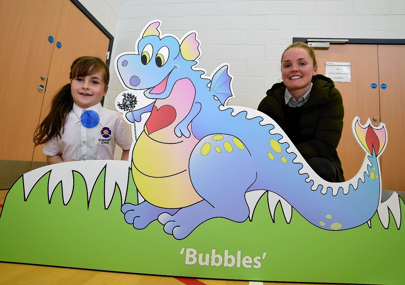 Rosehearty P4 pupil Kaelyn Simpson and Scotland international Kim Little with Bubbles the dragon.