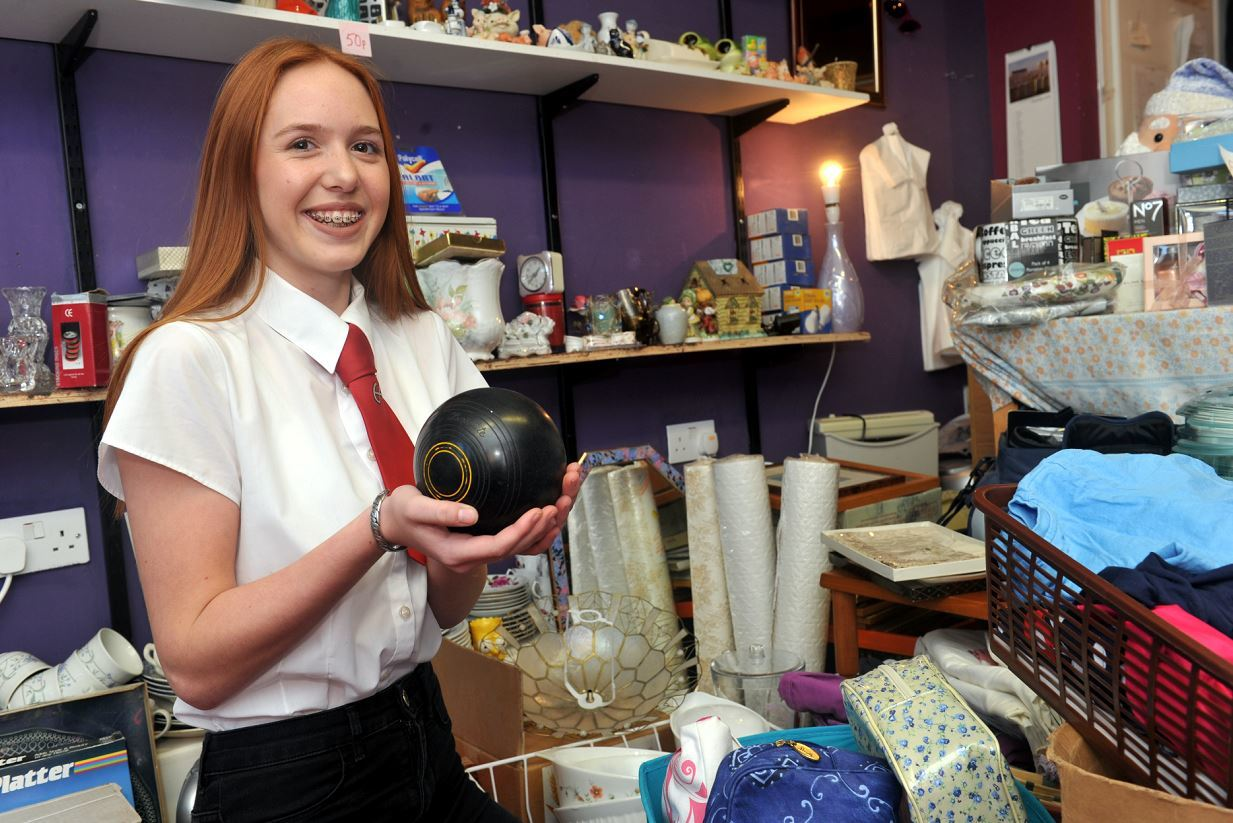 Eilidh Angus, in the charity shop she's running in Queen Street, Lossiemouth to help fund her trip to Mongolia, with a selection of items which have been donated for sale, including a set of lawn bowls. Picture by Gordon Lennox.