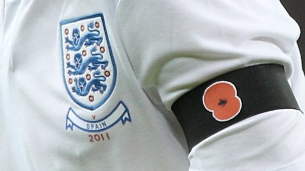 Detail of an England player wearing a black armband with a poppy symbol on aside the England badge