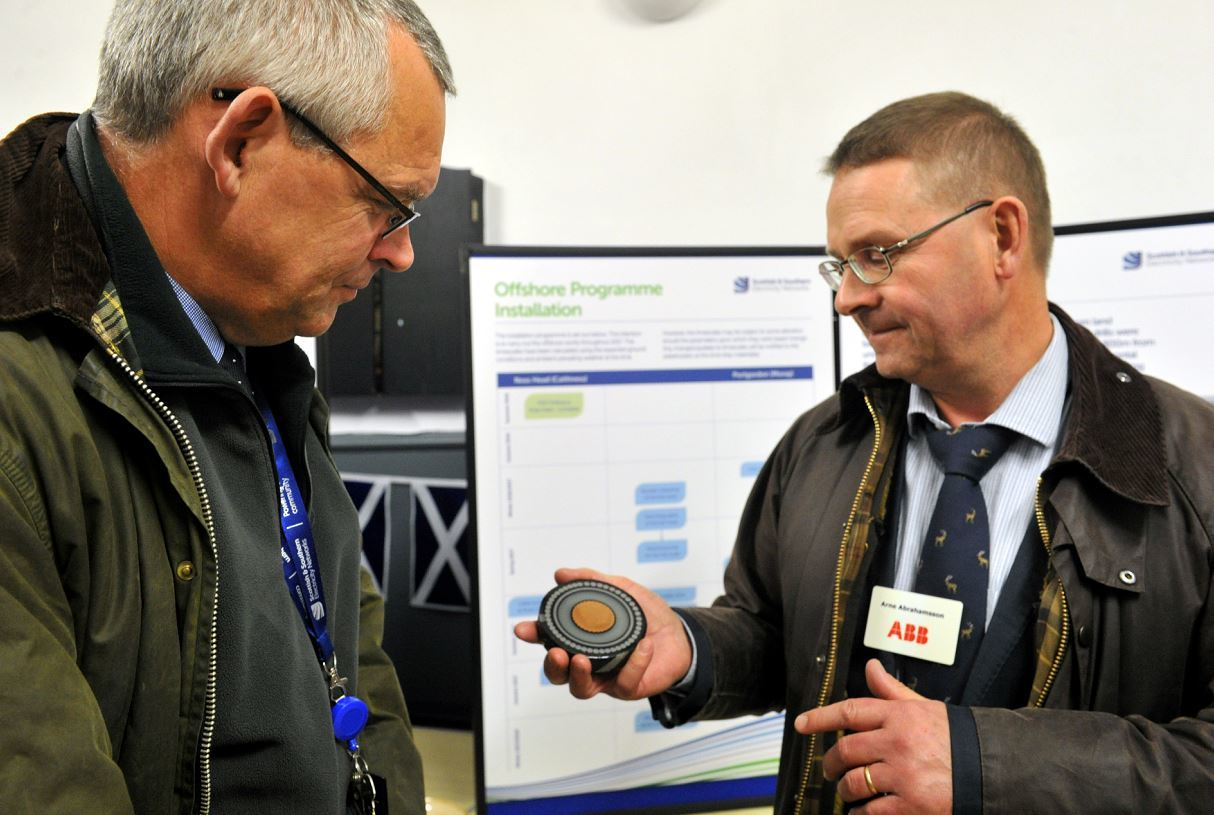 Public exhibition at Portgordon Village Hall regarding the subsea cale running from Caithness across the Moray Firth. Brian Mitchell, project manager SSEN, left, with Arne Abrahamsson, right, ABB project manager for the cabling system, showing Brian a cross section of the type of cabling being laid. Picture by Gordon Lennox.