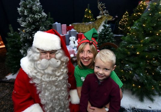 Santa Claus with Susan Crighton, fundraising manager at Clan and Adam Craik, 5, Portlethen. (Picture: Jim Irvine)