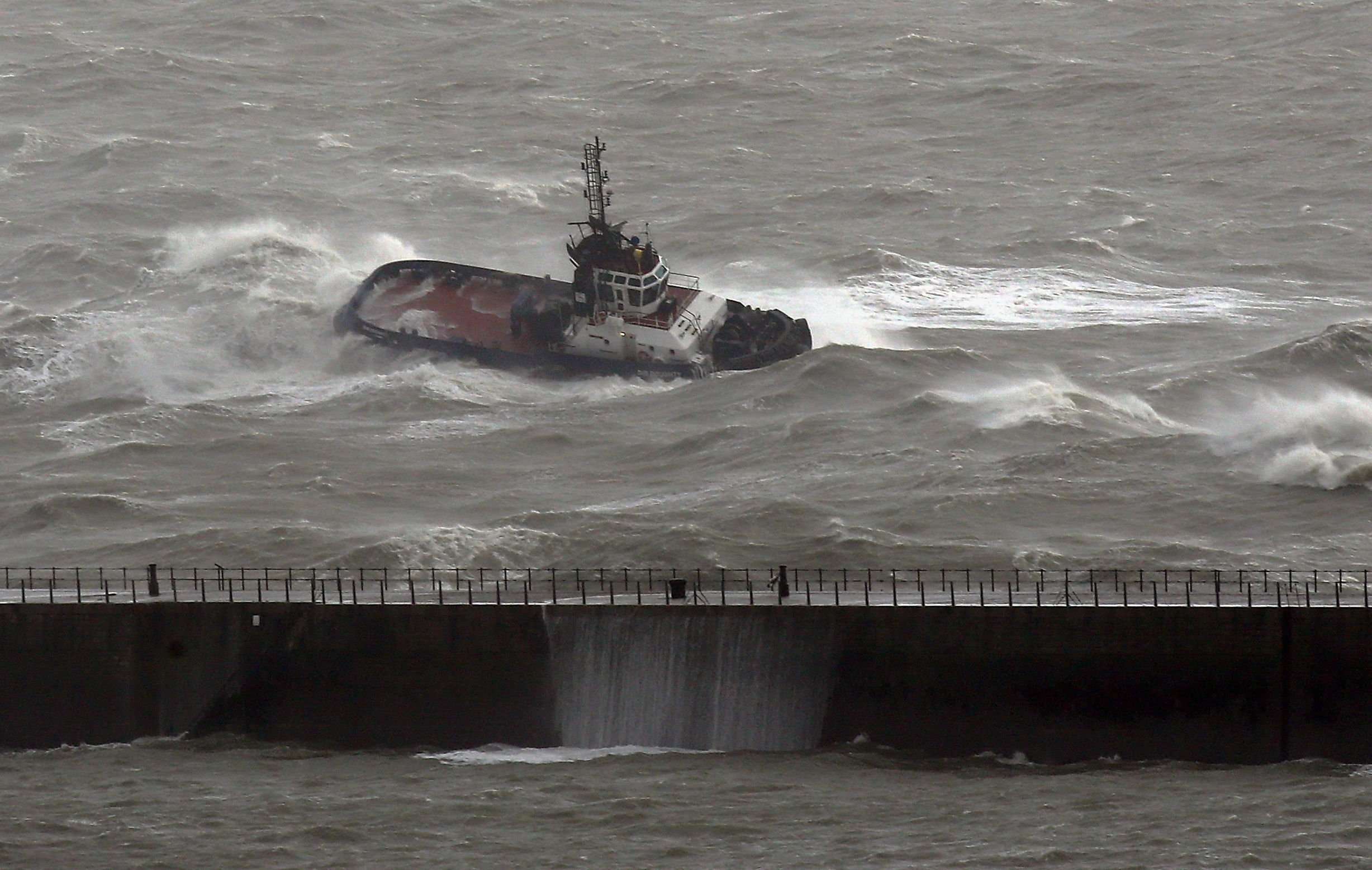 A Port of Dover tug crashes through waves in in Dover, Kent,