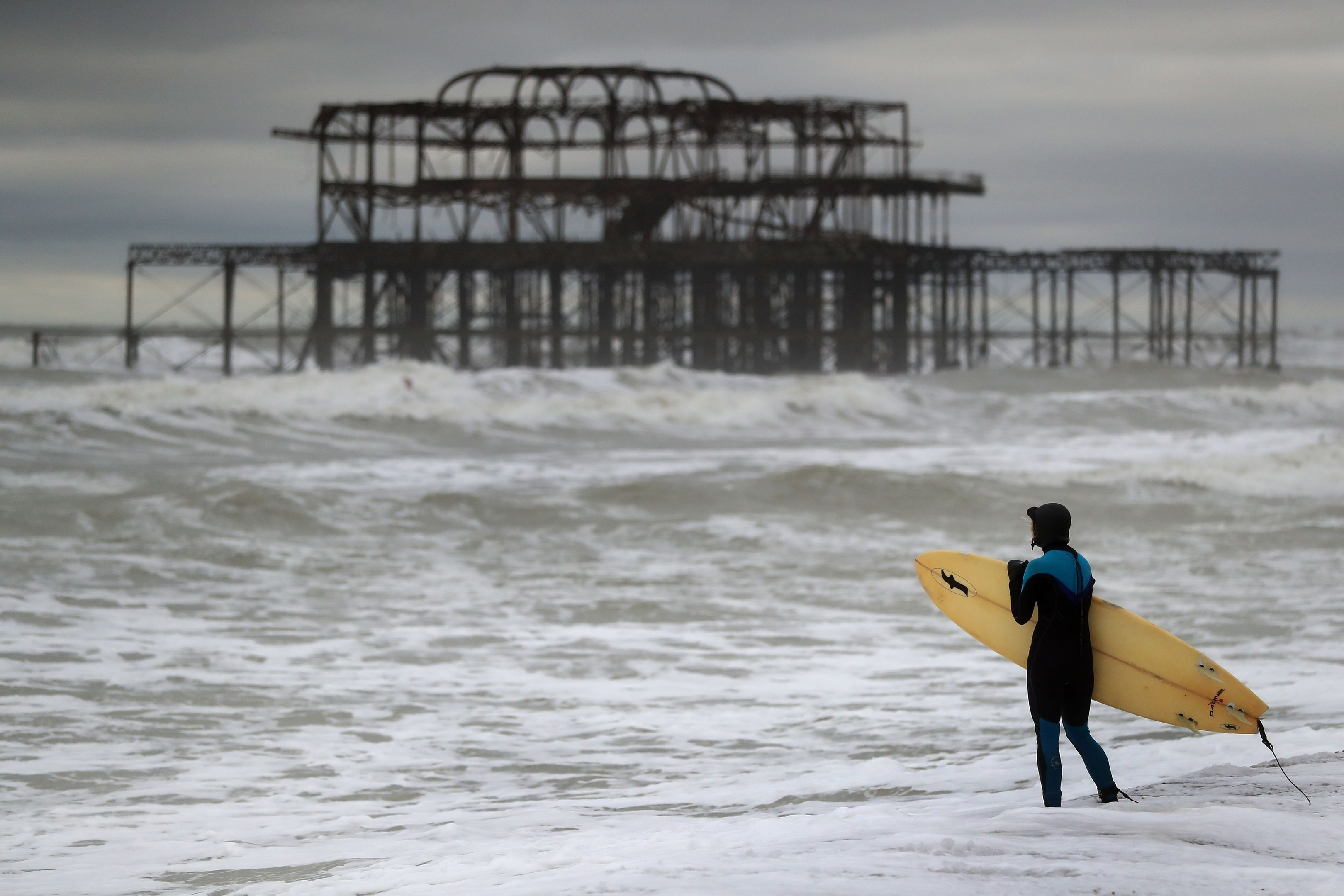 Strong waves surround the old West Pier in Brighton, Sussex