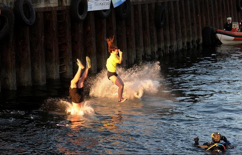 Swimmers run off the quayside at Burghead before swimming back to dry land.