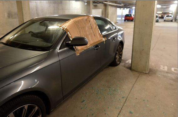 Glass litters the floor of the car park after this Audi A4 was broken into. Picture Jim Irvine