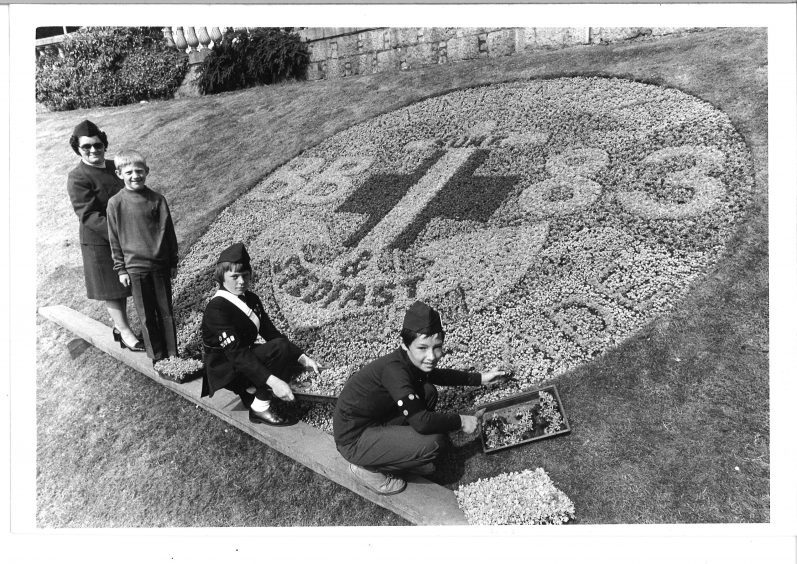 Flower display celebrates centenary year of Boys Brigade in 1983. In the picture is Florence Allan, Grant Davidson, Alan Diack and Alan Fraser
