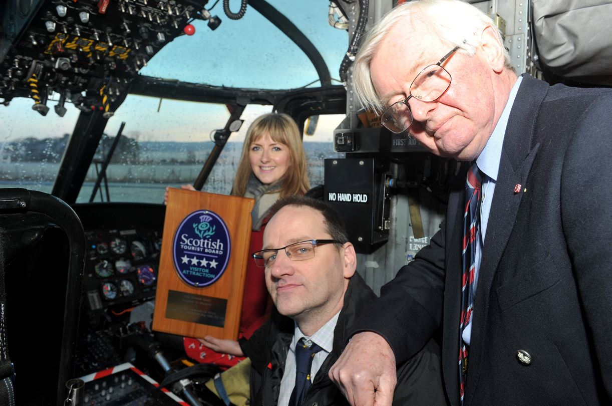Jo Robinson, Visit Scotland, in the captain's seat of Morayvia's star attraction, the Sea King helicopter, holding the four star award she presented to the aviation centre, with Mark Mair, centre, chairman of Morayvia, and Lord Lieutenant of Moray, Grenville Johnston, right.
