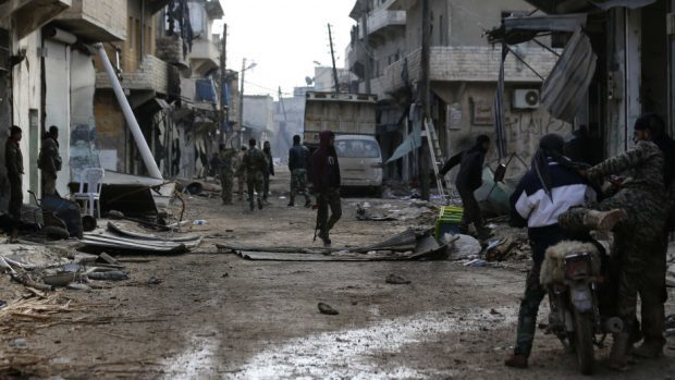 Syrian army soldiers patrol the east Aleppo neighbourhood of Tariq al-Bab (AP)
