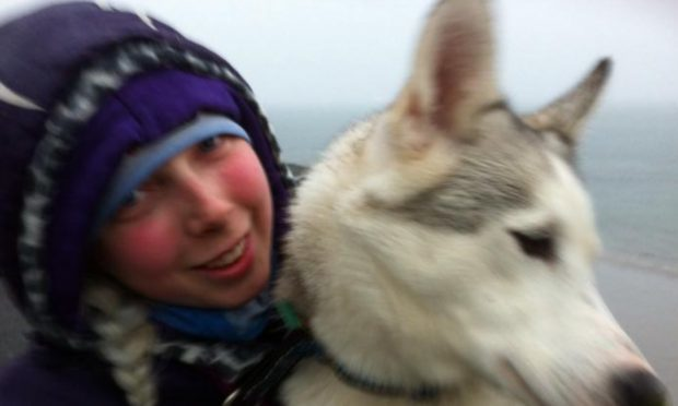 Rebecca pictured with one of her huskies (Image courtesy of Dundee Courier)