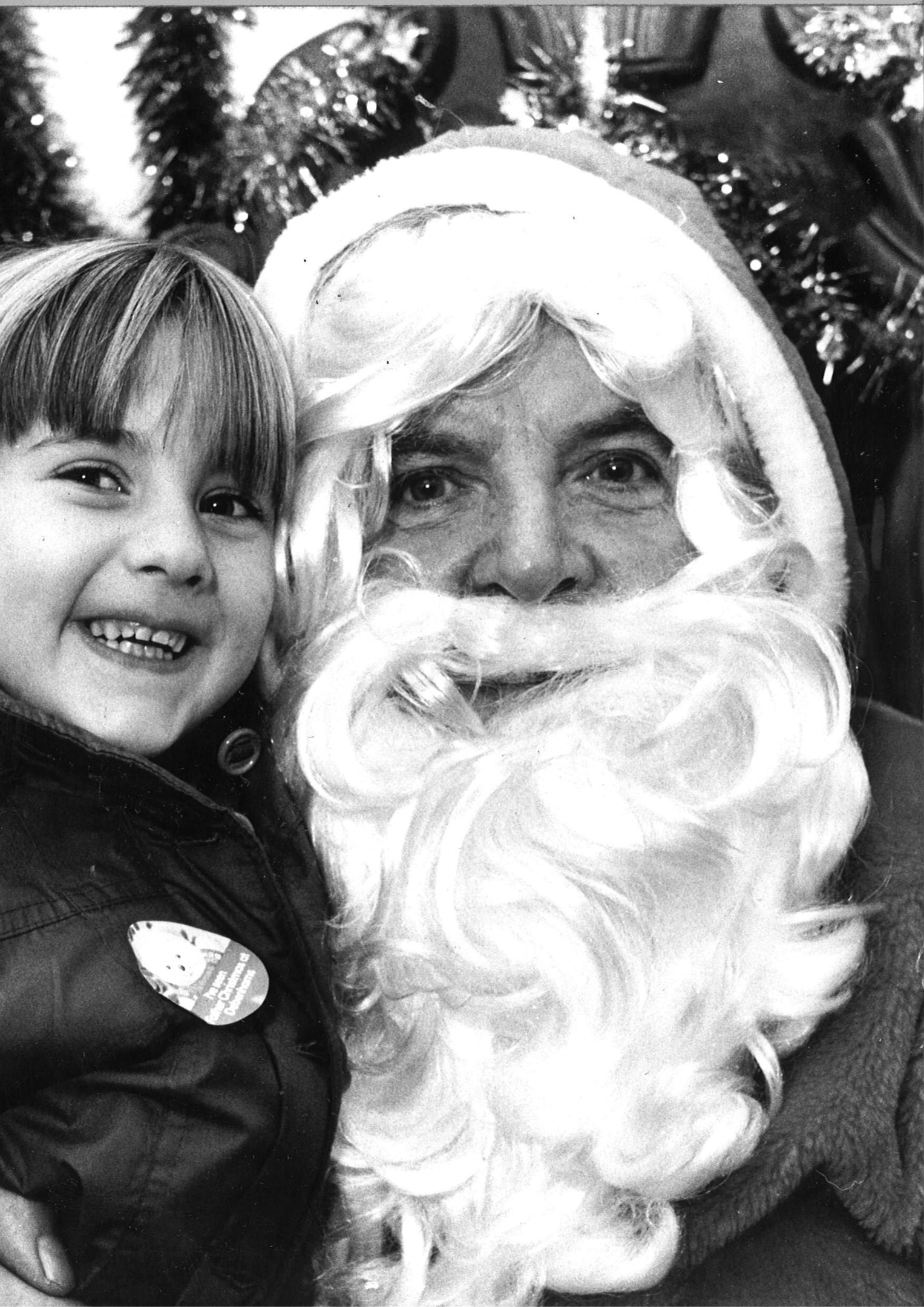 Cuddling up to Santa is Julie Wallace, aged 4