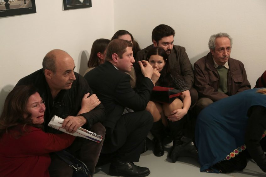 Pepole react after the  the Russian Ambassador to Turkey, Andrei Karlov,  was shot at a photo gallery in Ankara, Turkey, Monday, Dec. 19, 2016. A gunman opened fire on Russia's ambassador to Turkey at a photo exhibition on Monday. The Russian foreign ministry spokeswoman said he was hospitalized with a gunshot wound. (AP Photo/Burhan Ozbilici)