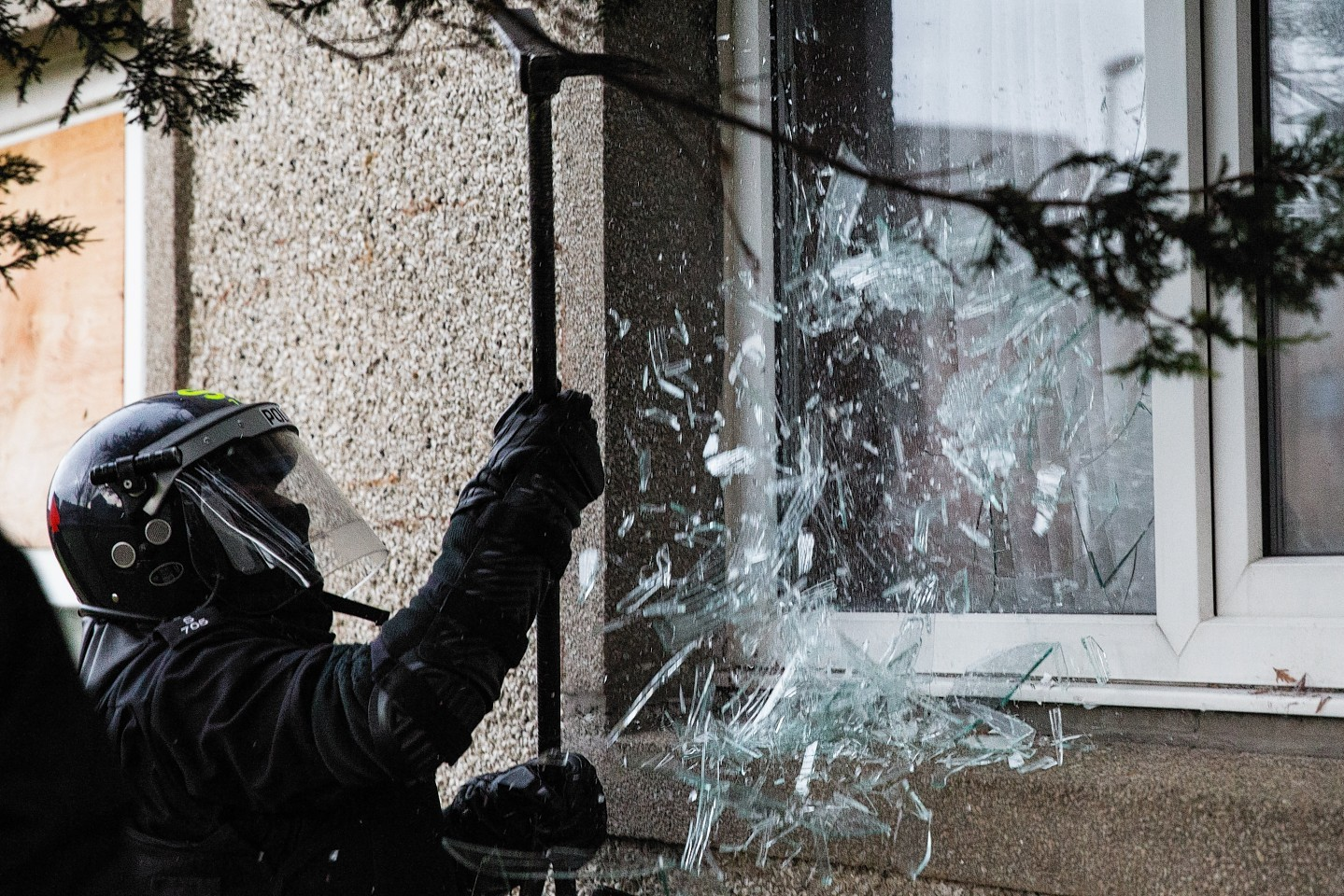Police break a window to gain entry into a raided property.