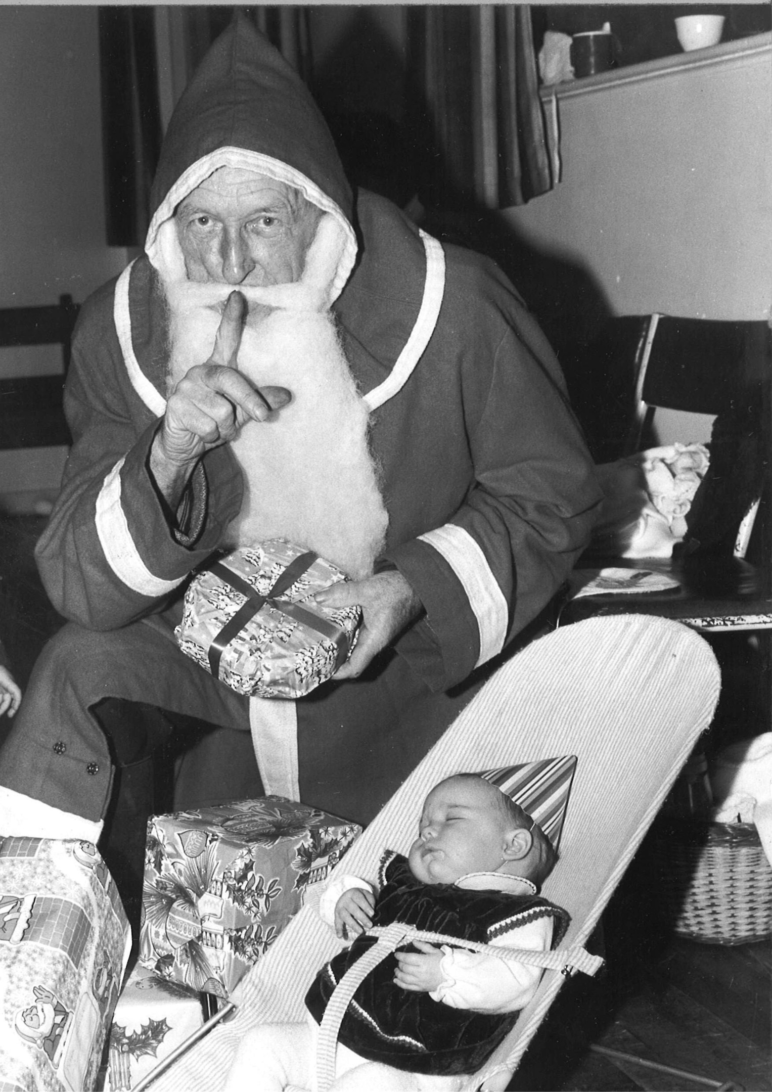 Totally oblivious to Santa during his visit to the Mothers' and Toddlers' group party at Torphins is Michelle Duguid. 1983.