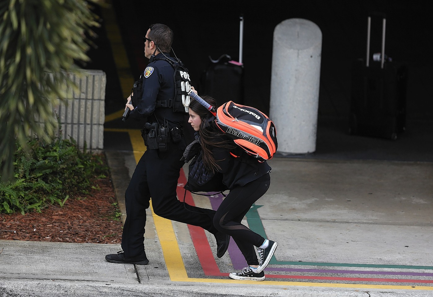 A young woman runs behind a police officer as they seek cover outside of Fort Lauderdale-Hollywood International airport