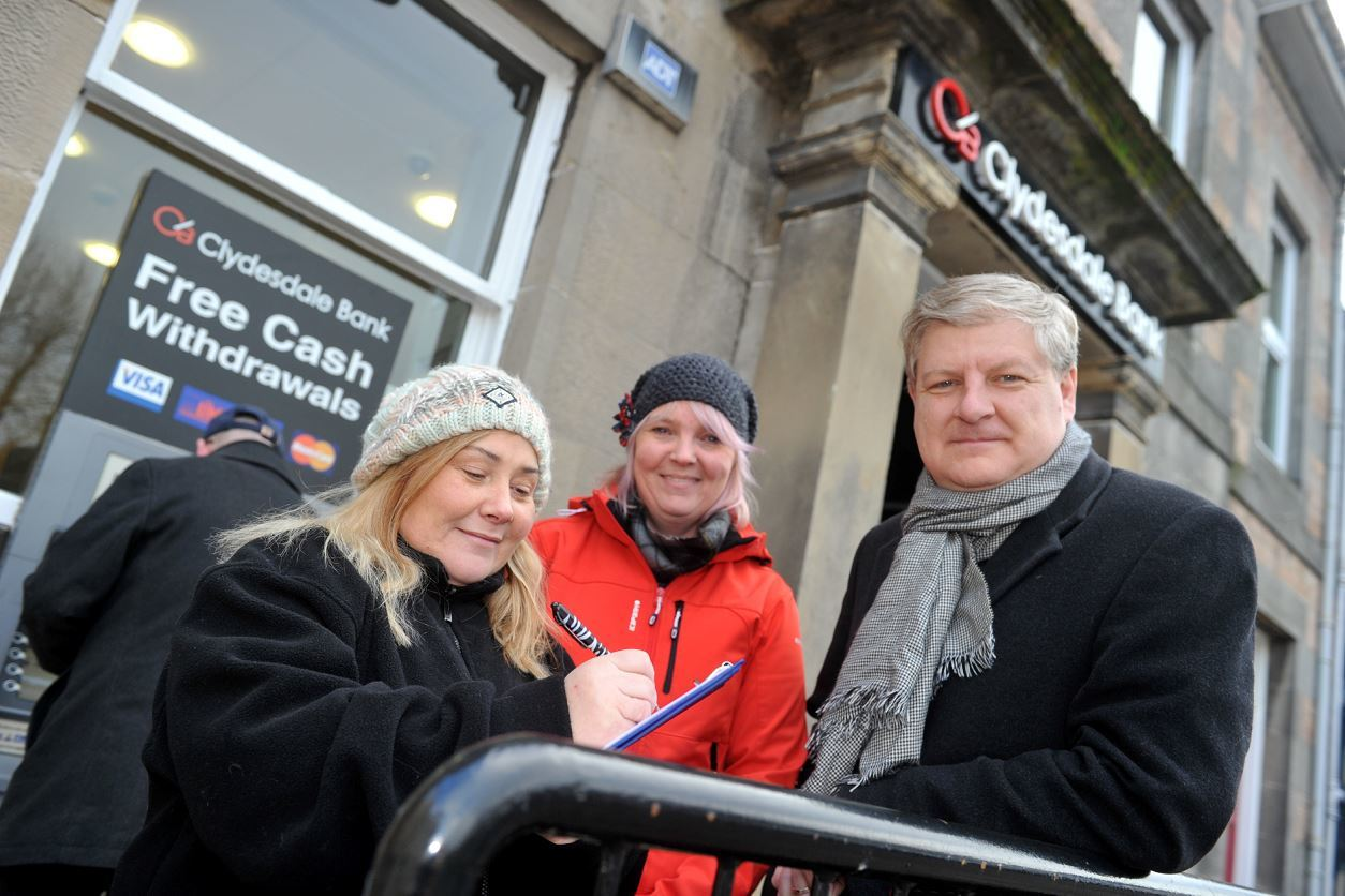Angus Robertson MP, supporting Louise Laing, centre, collecting signatures to save the Clydesdale Bank in Aberlour as Pauline Younie, left, signs the petition.
