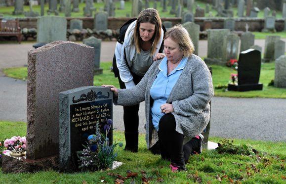 Mary Dalziel (righ) at the grave of her husband Richard with her daughter Lynda Moonan, at the Banchory-Ternan Kirkyard, Banchory. Credit: Kami Thomson.