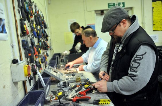 Volunteers at Reboot in Forres working on the bench - breaking computer equipment for scrap. Picture by Gordon  Lennox.