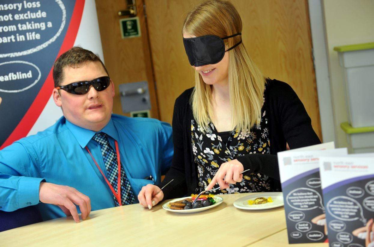 Lara Mackay struggles to find anything on the plate at North East Sensory Support, having been blindfolded to simulate blindness, with Bruce Cruickshank, fundraising assistant, Ness. Picture by Gordon Lennox