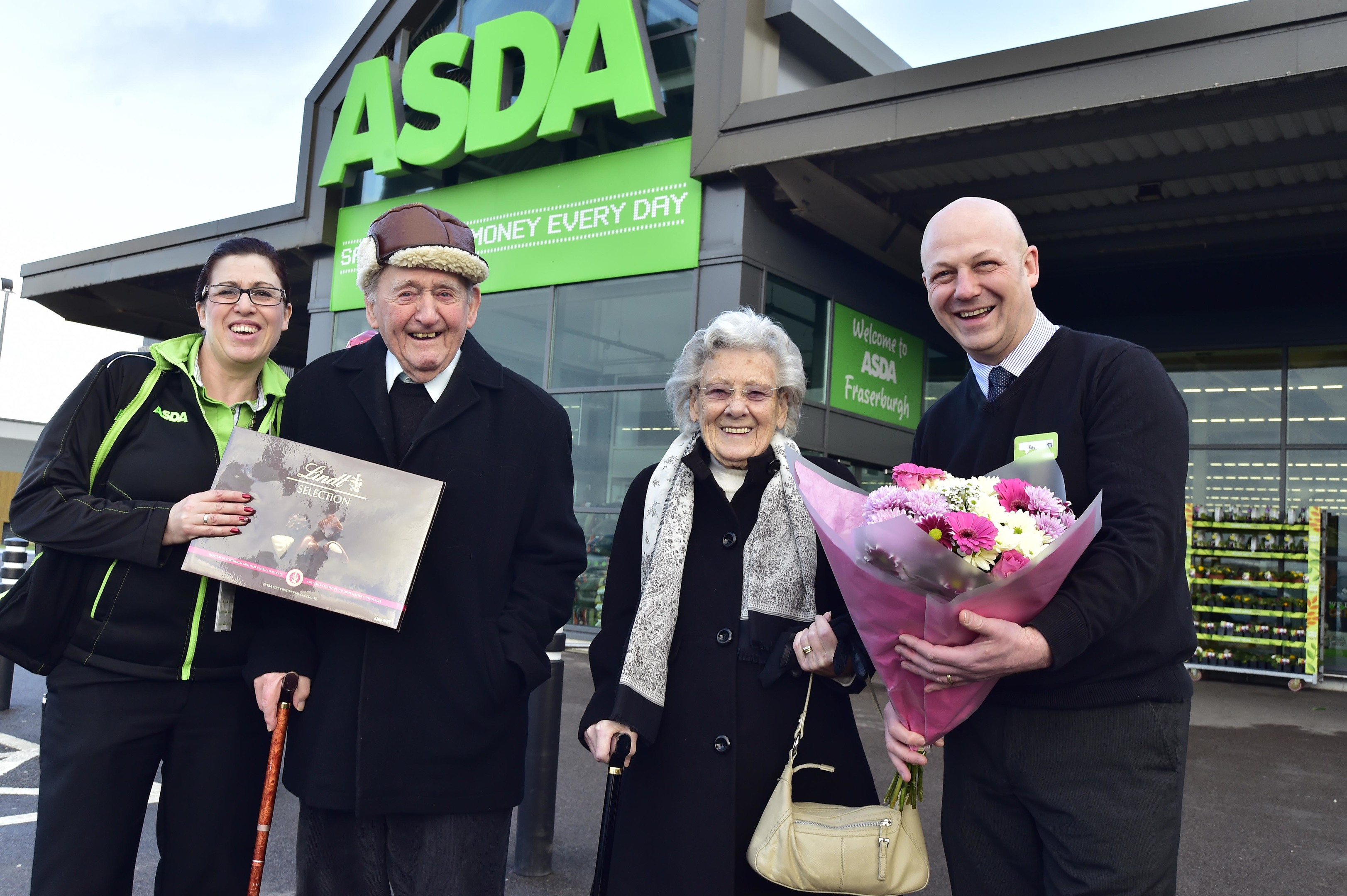 FRASERBURGH COUPLE BOB AND GINA MCDONALD RECEIVE GIFTS FROM ASDA MANAGER EDY YOUNG AND COMMUNITY CHAMPION CAROLYN TAYLOR TO MARK THEIR 70TH WEDDING ANNIVERSARY