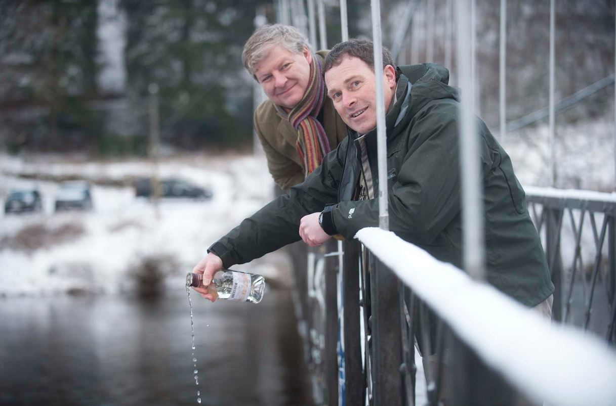 Moray MP Angus Robertson and Graham Ritchie, who caught the first salmon of the season last year, pour whisky into the River Spey to open the new season.