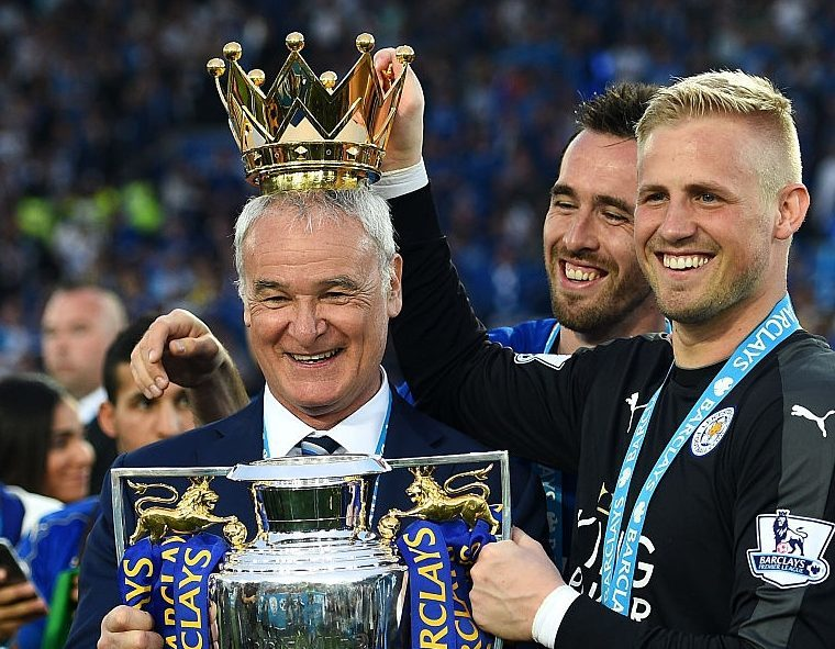Claudio Ranieri poses with the Premier League Trophy while Kasper Schmeichel puts the crown on the head of the manager