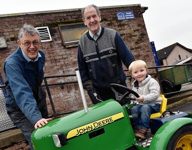 Three year old Alfie Mearns with the toy tractor his grandfather Bob Mearns (centre) made for his dad. Jim Wilson, one of the Men's Shed workers (pictured) did most of the work to refurbish it. Picture by Colin Rennie.