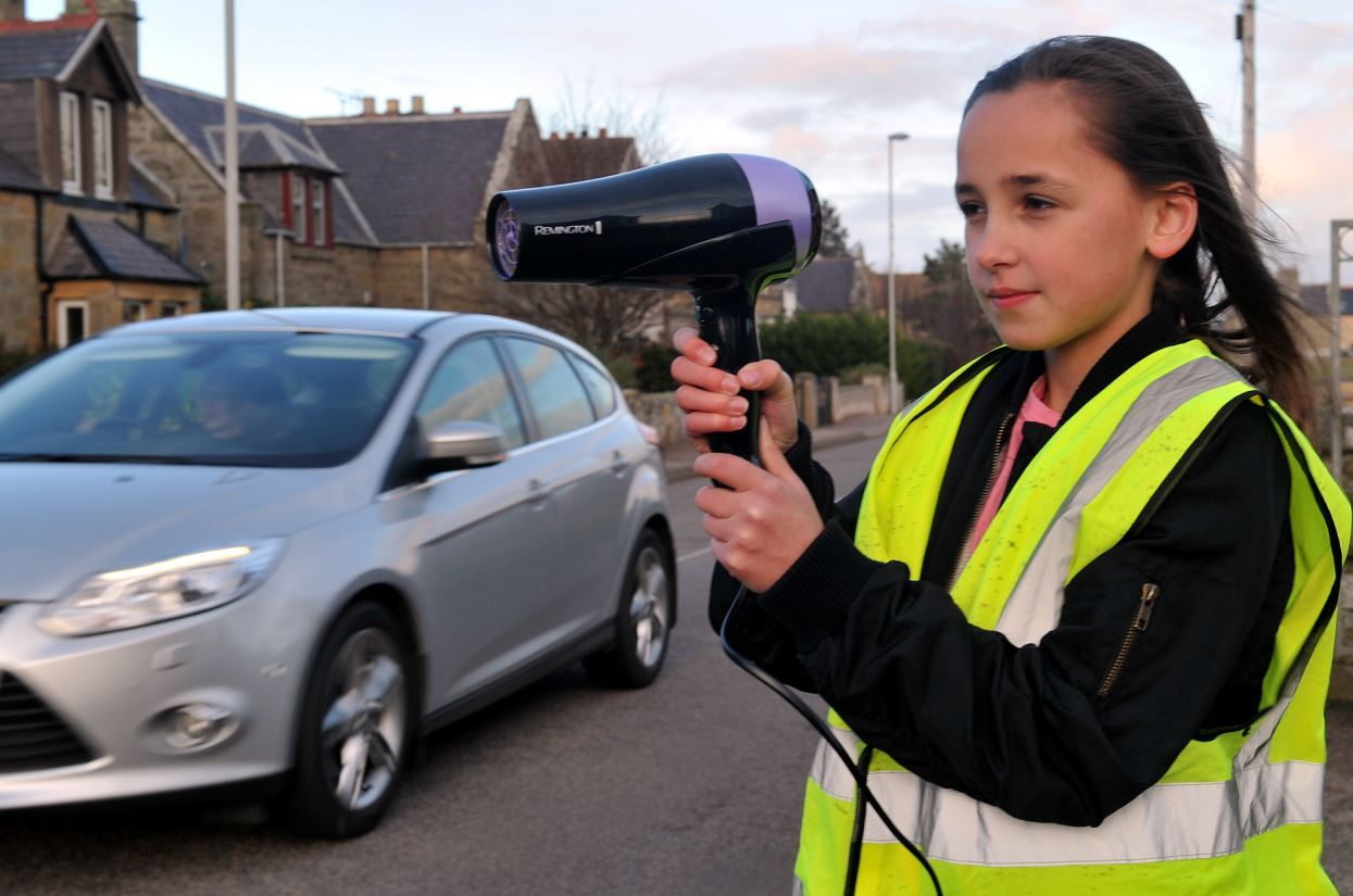 Erin Hepburn, 10, points a hair dryer to mimic a speed gun on Forsyth Street in Hopeman.