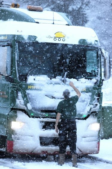 A lorry driver clears his windscreen and wipers of snow at Moy.