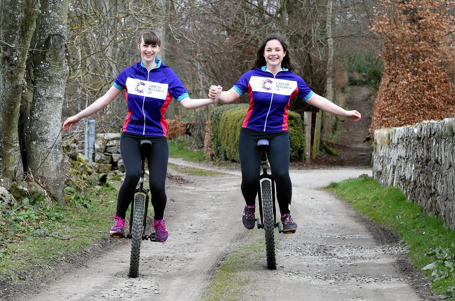 Fundraisers Iona Copley and Gemma Shaw on their unicycles.