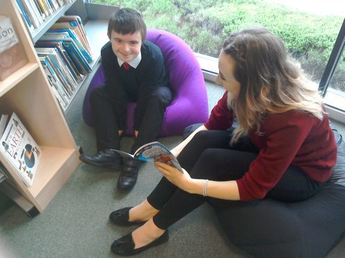 Elgin Academy student Kayleigh Young works with Bruce to build his confidence in reading.