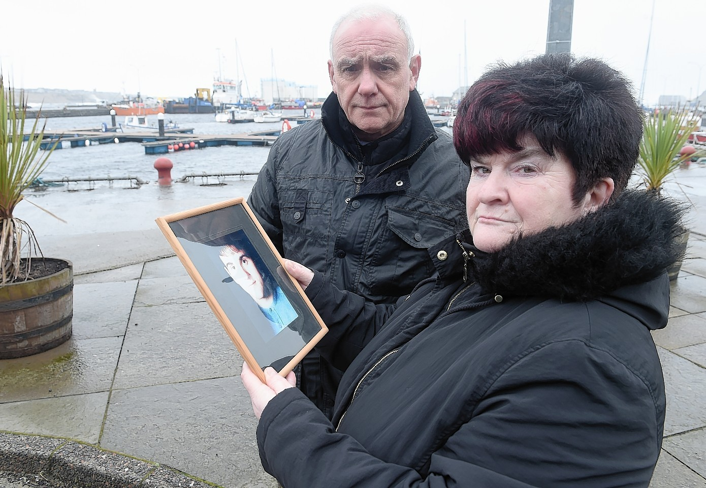 Hugh and June McLeod with a photograph of their late son Kevin at the scene in Wick Harbour  where the fatal incident took place.