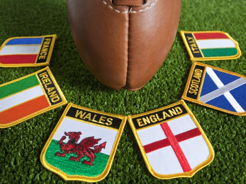 The Six Nations Championship is an annually contested rugby union competition involving six European teams, England, Ireland, Scotland, Wales, France and Italy, as depicted by the 6 National Flag badges on the grass pitch background.