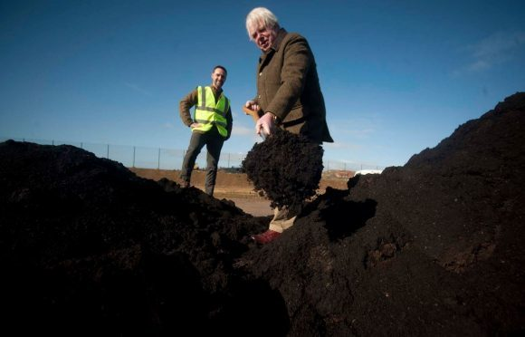 Findhorn and Kinloss community councillor Harvey Morton helps himself to the compost.