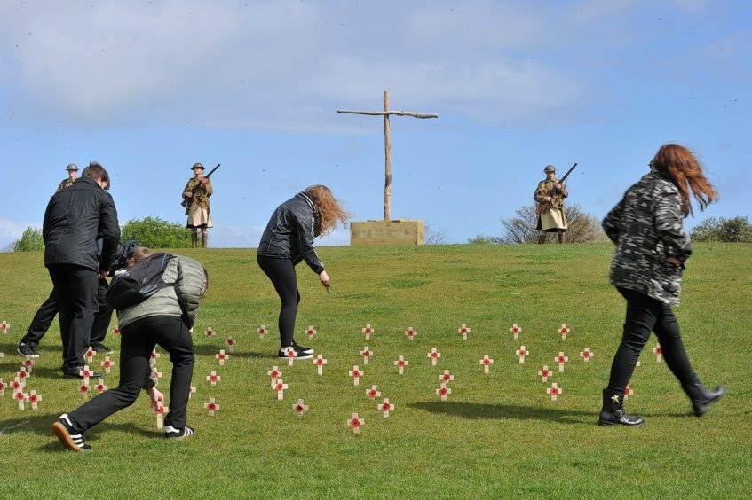School pupils place crosses in memory of the dead.