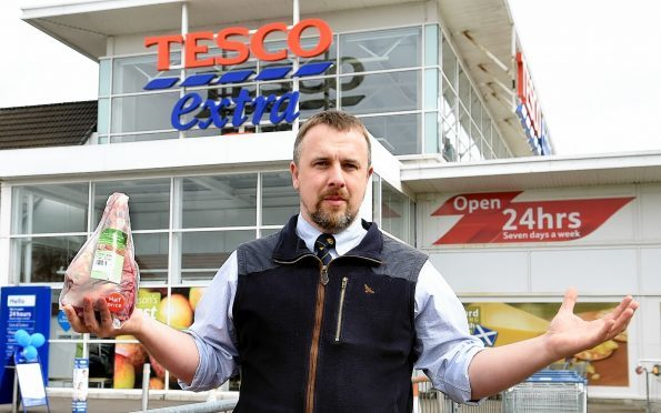 John Fyall holds a leg of New Zealand lamb outside the Tesco store in Aberdeen.