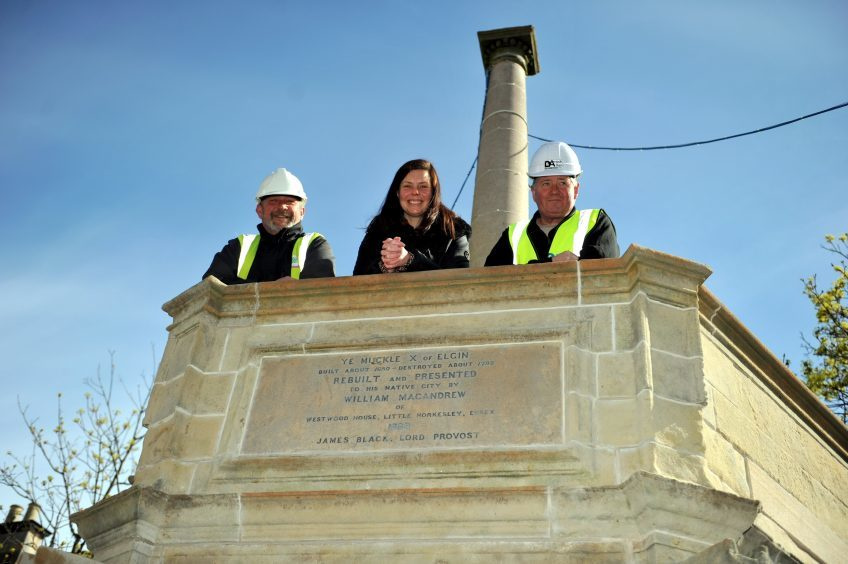 L-R: Jez Allum, Ellen Cox, Conservation Area Regeneration Scheme, and David Box, Darroch & Allan, on the refurbished Muckle Cross.