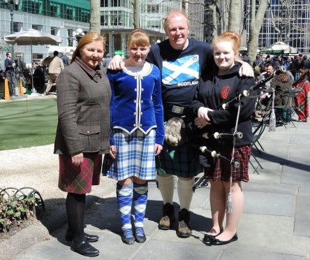 Elizabeth (right) played the bagpipes during the New York Tartan Day Parade, while her younger sister Anna performed with the New York Highland Dancers. Pictured here with their parents.