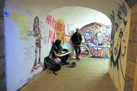 A young musician busks for change in a graffiti-lined passageway in Olomouc, Czech Republic. Approximately 25,000 attend university here. Copyright Amy Laughinghouse.