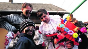 A man shows a young boy his masopust mask. All ages take part in this pre-Lenten celebration in the Czech town of Vortova. Copyright Amy Laughinghouse.