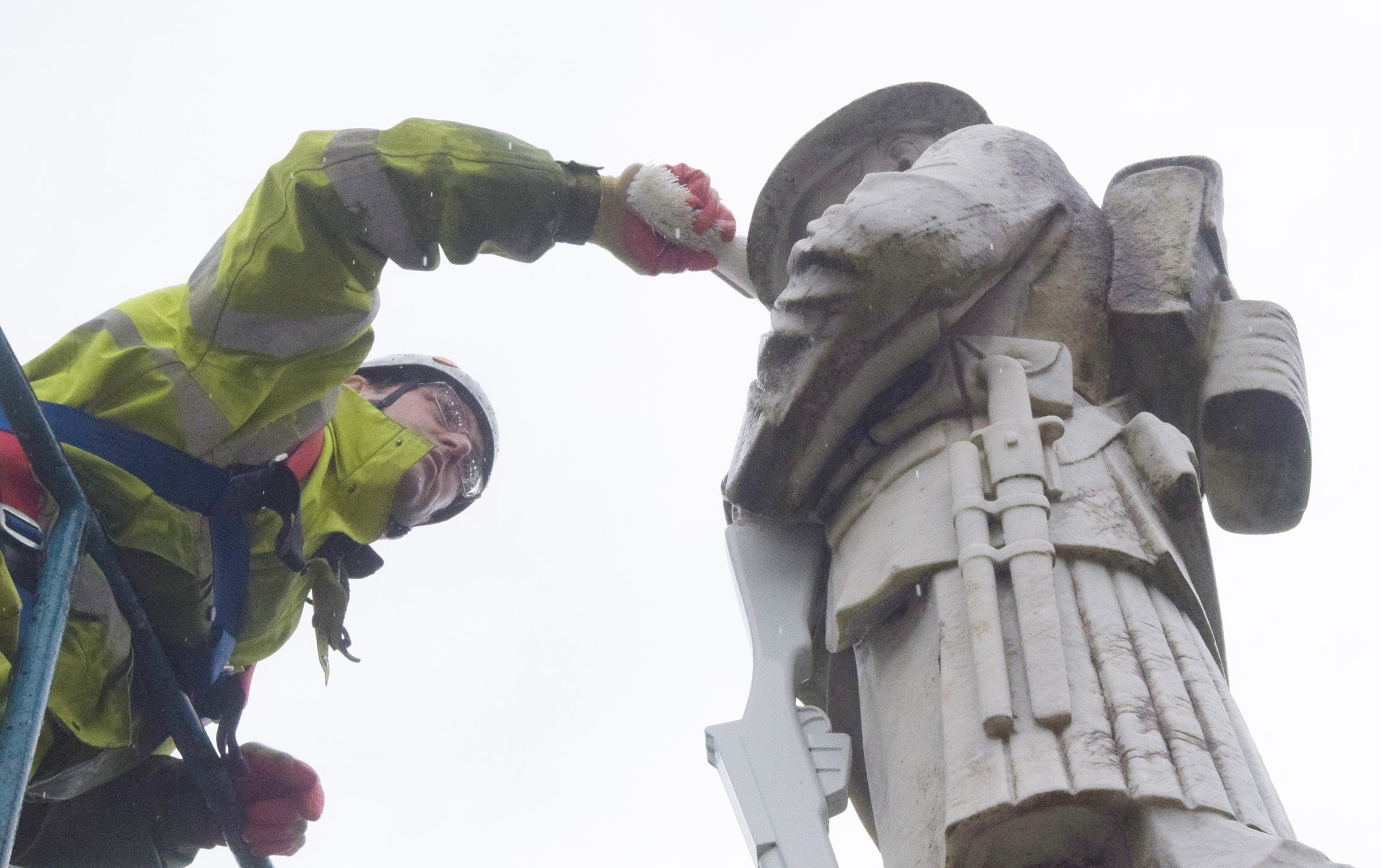 Face to face with the marble soldier, Calum Ross cleans off years of grime from the Fort William war memorial.