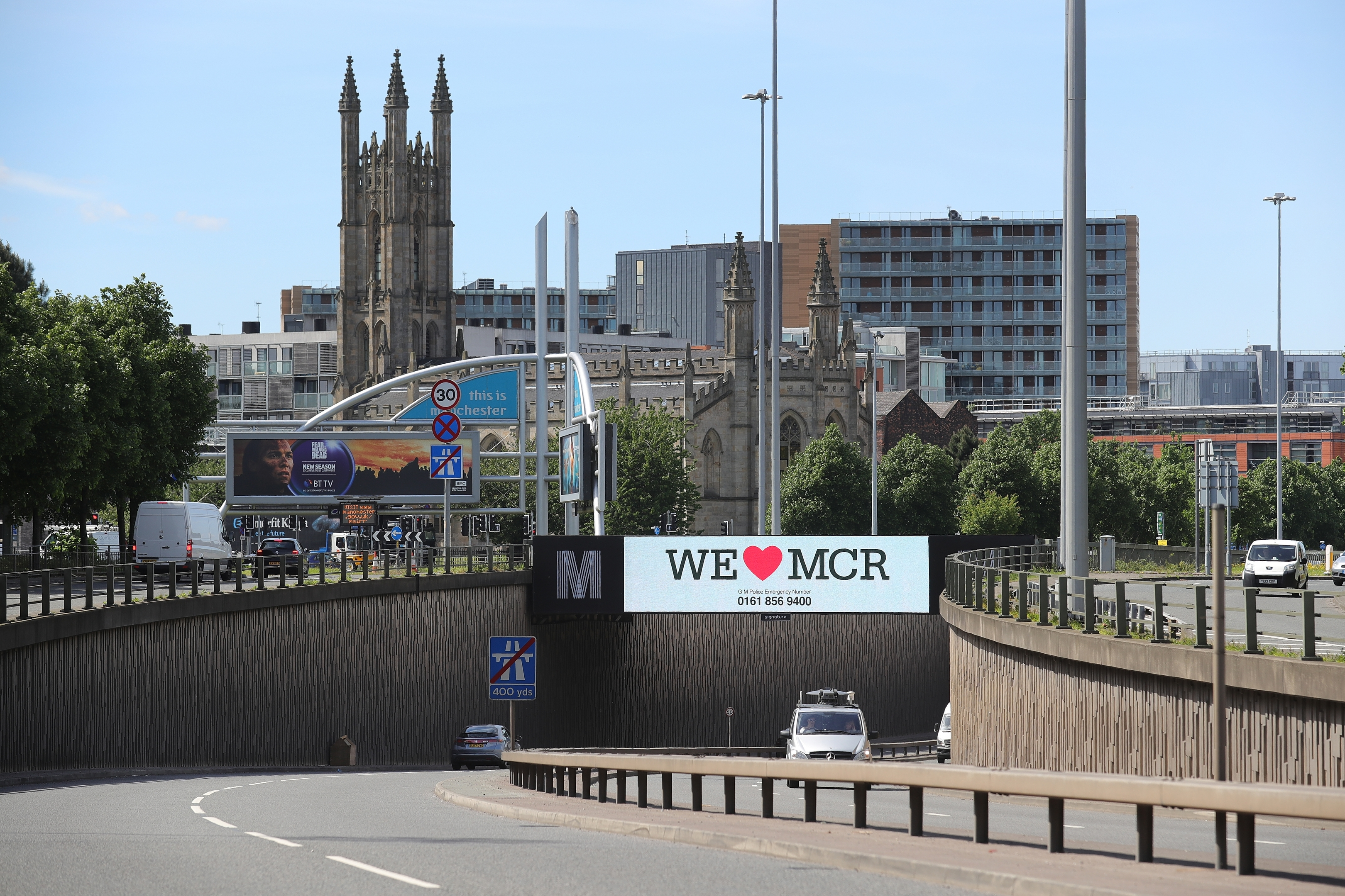"""A giant TV screen displays the 'We Love Manchester"""" logo and police emergency incident telephone number"""