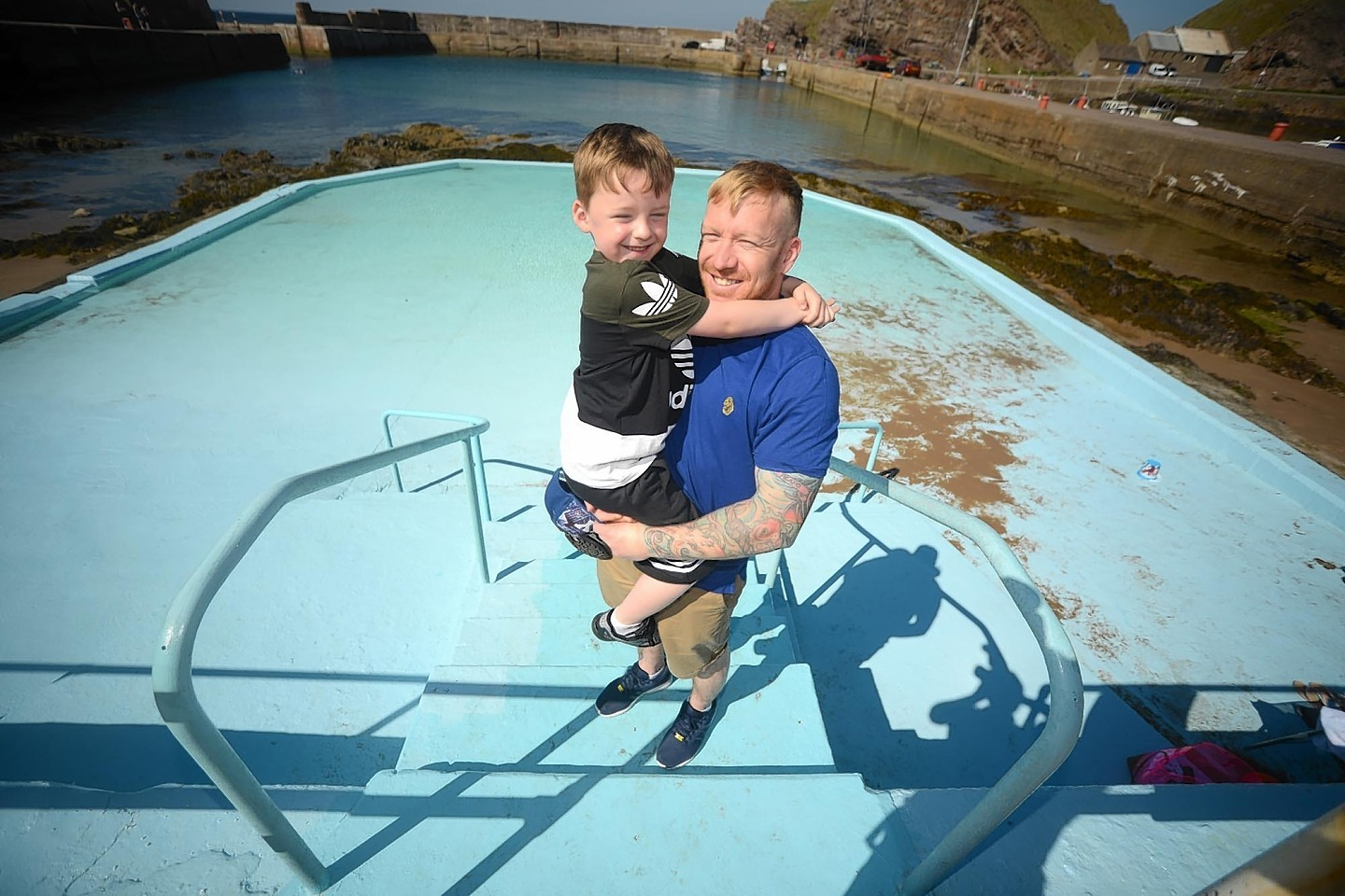 Steven Farquhar helps look after Portknockie at the paddling pool he has just finished doing it up for summer.  Also in the photo is his son Alex, 5